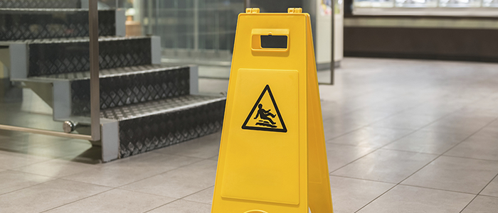 Yellow wet floor sign placed by stairs