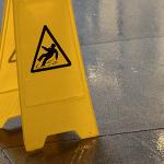 Yellow wet floor sign on gray tiled floor
