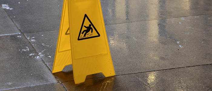 Yellow wet floor sign on gray tiled floor