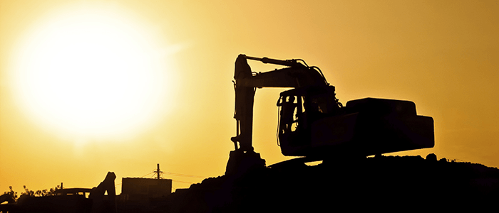 Yellow setting sun forms a black silhouette of outdoor workers with construction crane