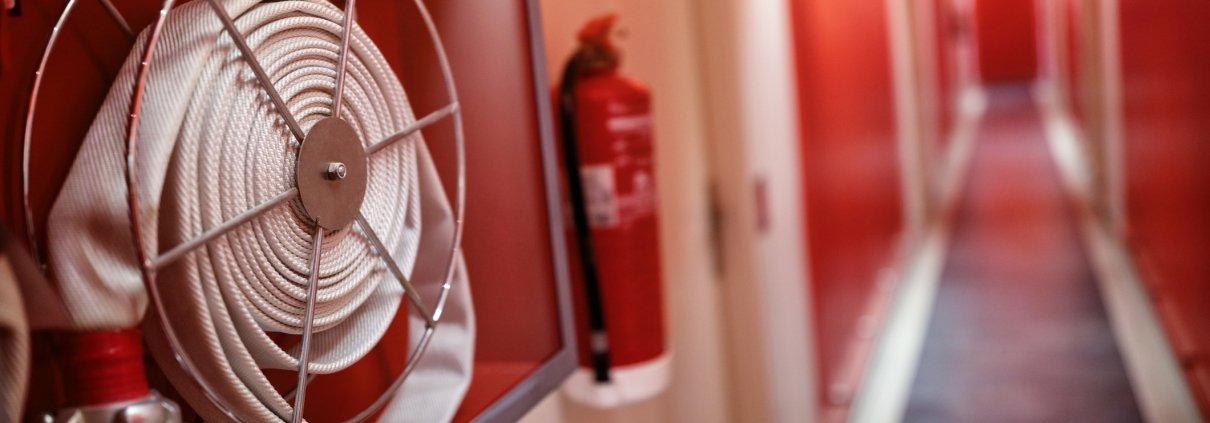 White emergency fire hose and fire extinguisher in a red hallway