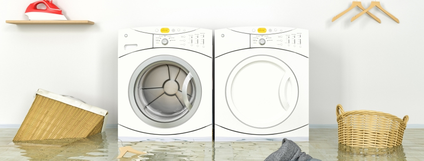 Laundry room with white washer and dyer flooded with hampers floating in water
