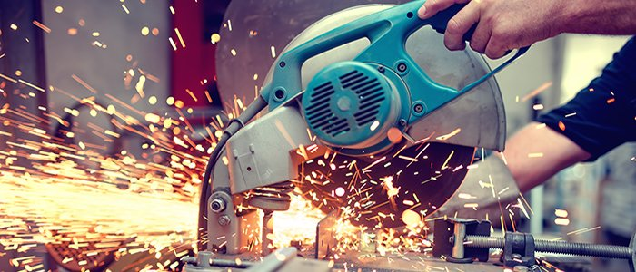 Sparks fly as mechanic uses electrical saw to cut through metal