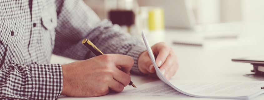 Male Business owner sitting at table and signing contract