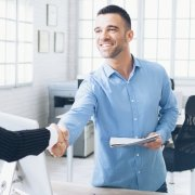 Male and female business owners shaking hands with an insurance broker
