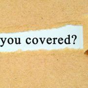 "A ripped piece of brown paper to reveal the words ""are you covered"" typed underneath"