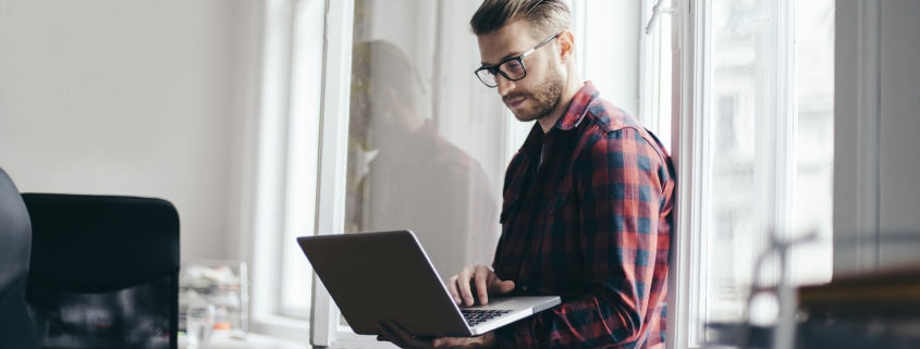 Male business owner standing with laptop in hand