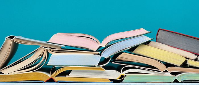 Open stack of pastel coloured books piled against a turquoise background