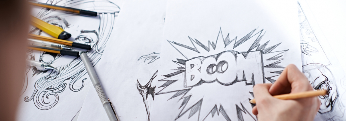 "A comic book artist writing ""BOOM"" on a piece of paper"