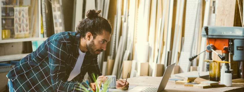 Male business owner reviewing delivery list on laptop