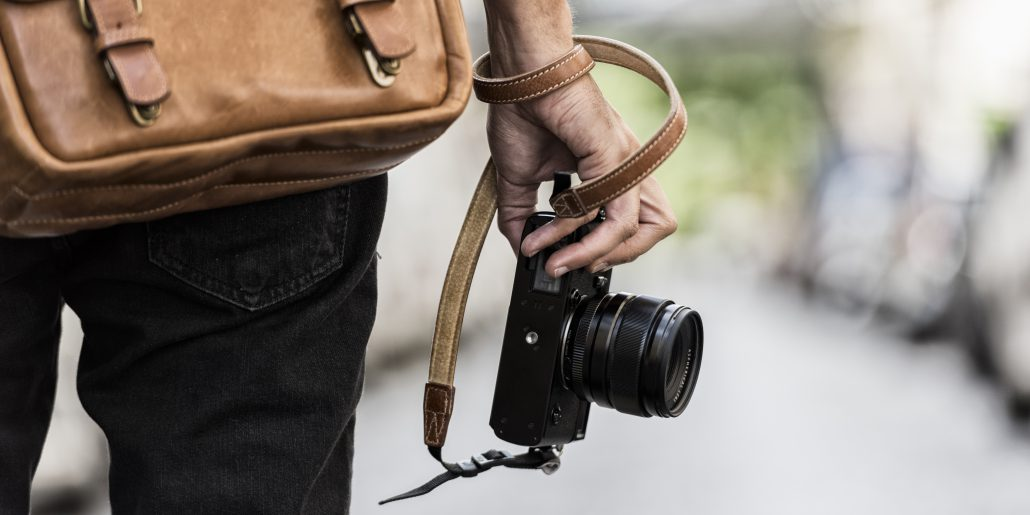 Photographer wearing a brown bag holding a black camera with straps warped around his wrist.
