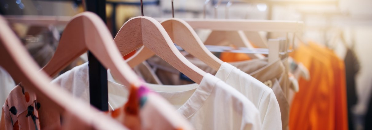 Bright colourful clothes hung with wooden hangers on clothing rack