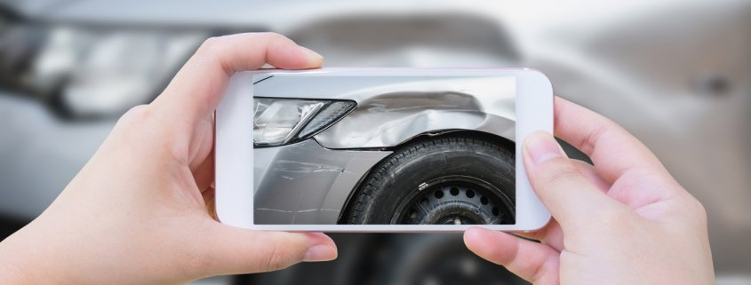 Person taking picture of a dented car with smart phone