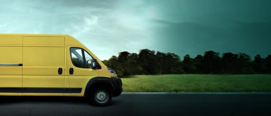Yellow commercial van driving towards a stormy road