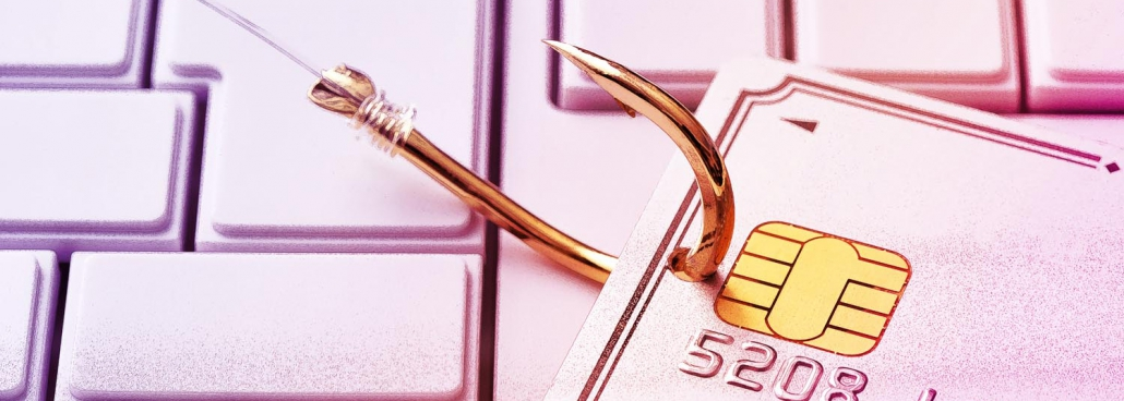 A credit card hooked on a golden hook on top of a keyboard