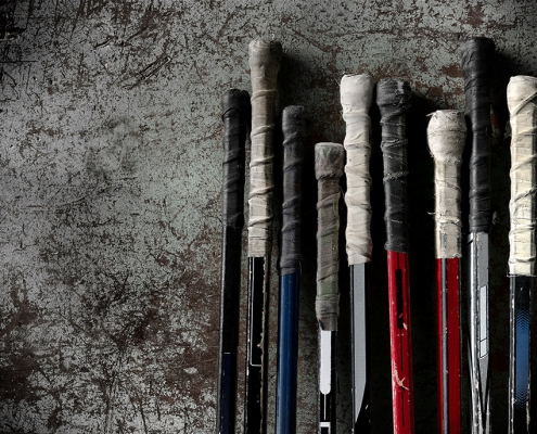 row of hockey stick handles leaning against a grey wall