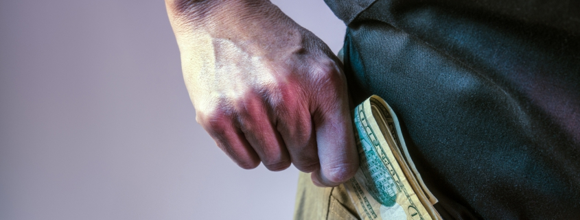 Close up of person holding money putting inside their pocket