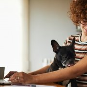 Smiling women with her laptop looking at a black dog sitting on her lap.