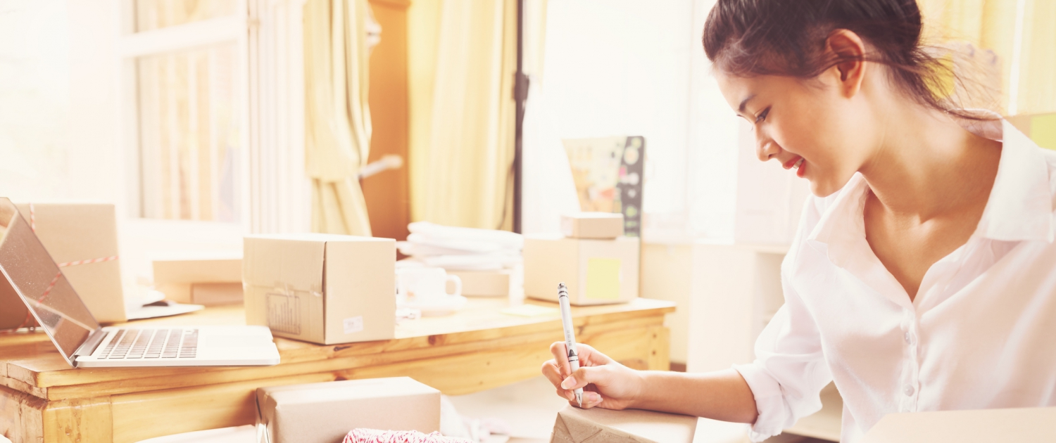 A female business owner at her office writing a label on a package