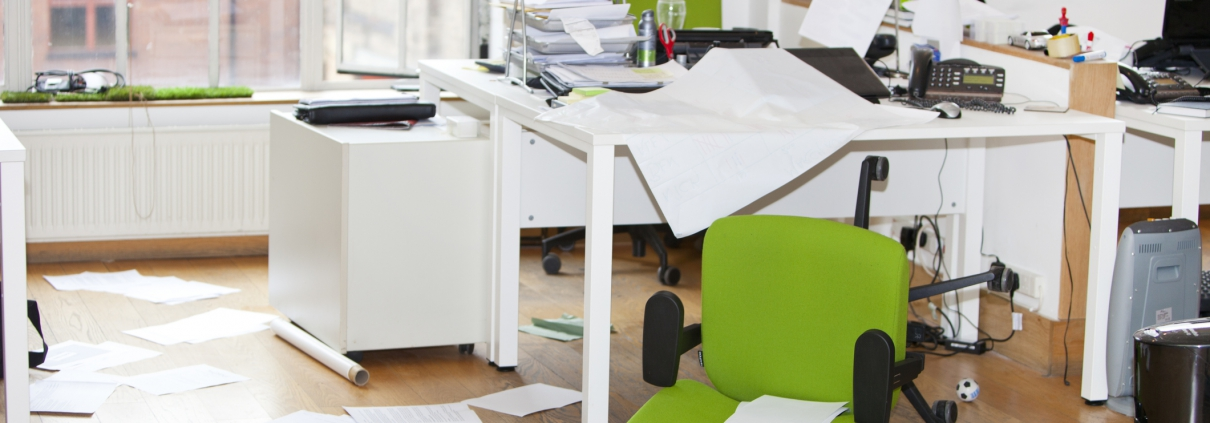 A messy office desk with a green chair knocked over and papers all over the floor.