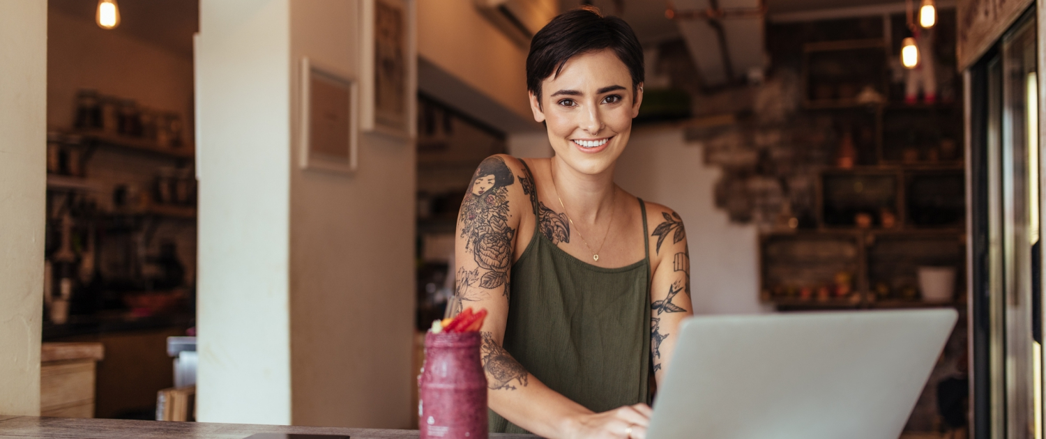 Happy women with arm tattoos on her laptop smiling