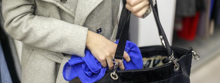 A woman placing a stolen shirt in her purse.