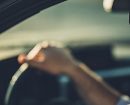 hands on a steering wheel of a car in motion