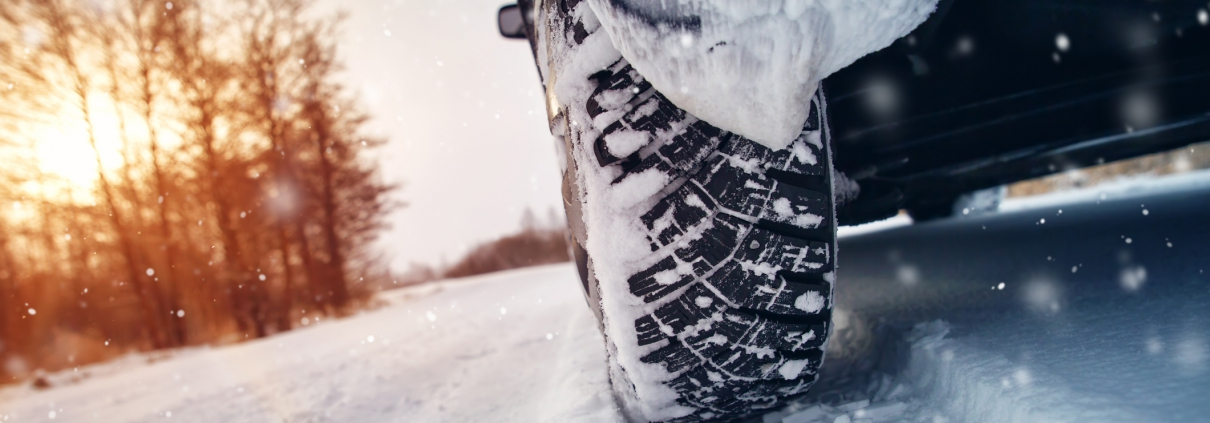 Car tires on winter road covered with snow.