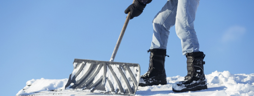 A man shoveling snow off of a roof