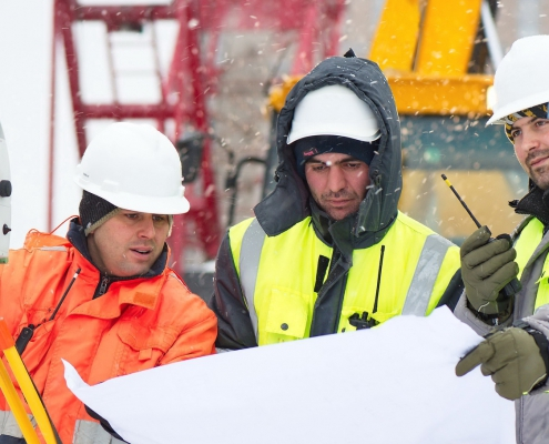 Workers working at a construction site in cold temperatures.