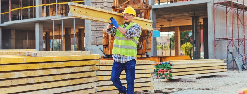 male construction worker carrying plank